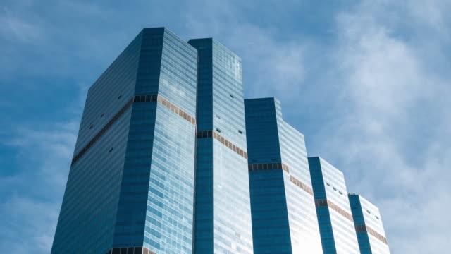 vidéos et rushes de time-lapse : business buidling avec des nuages reflétés dans les nombreuses facettes miroir, résolution 4k. - quartier de bureaux