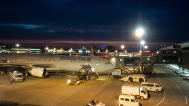 vídeos de stock, filmes e b-roll de lapso de tempo: elevador do carro da carga e bens e malas do carregamento ao avião no aeroporto no crepúsculo. zoom out shot - embarcar
