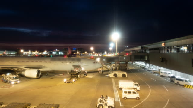 time-lapse : cargo car lift and loading goods and luggages to the airplane at the airport at twilight - vehicle part stock videos & royalty-free footage