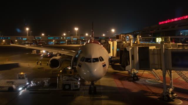 vídeos de stock, filmes e b-roll de time-lapse: carro de carga carregando bagagem do avião no aeroporto à noite - embarcar