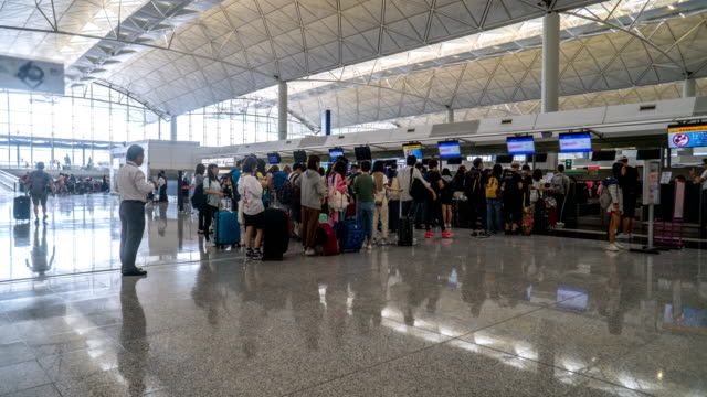 4k timelapse - check-in queue in hong kong airport - waiting in line stock videos & royalty-free footage
