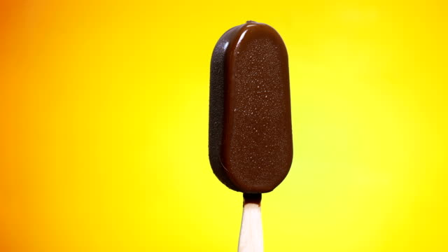 vídeos de stock e filmes b-roll de time-lapse: chocolate coated ice cream melting on yellow background - fundição