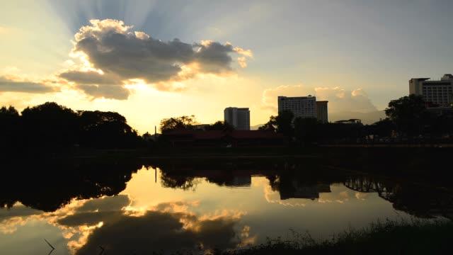 Zeitraffer: Stadtansicht Silhouette mit Sonnenstrahl Reflexion auf den Fluss