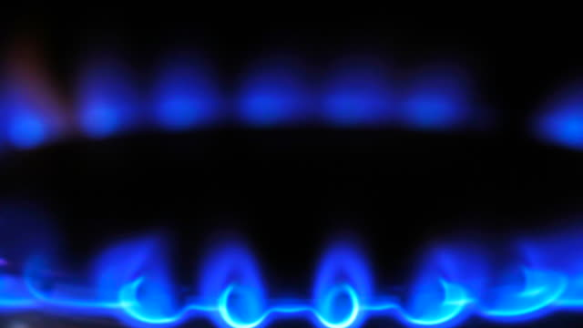 Timelapse close up tilt down of flames on a gas ring on a natural gas cooker