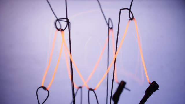timelapse close up zoom into an electric light bulb filament flickering on and off - ケーブル線点の映像素材/bロール
