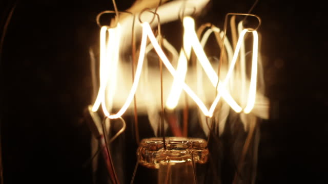 timelapse close up zoom out and track up of an electric light bulb filament flickering on and off - lampada elettrica video stock e b–roll