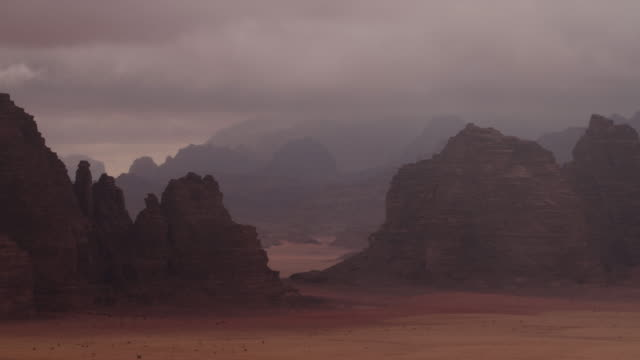 Timelapse cloud and sunbeams drift over mountains in desert, Wadi Rum, Jordan