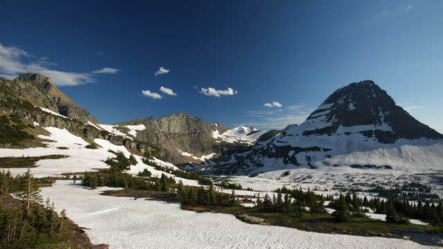 Timelapse cloud drifts in blue sky over Rocky Mountains and snowy valley, Montana, USA