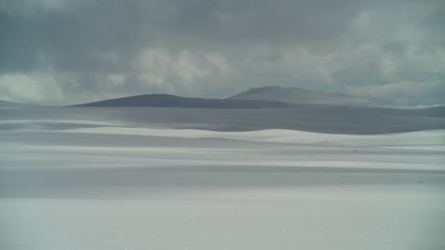 Timelapse cloud shadows drift over snowy mountains and tundra, Sweden