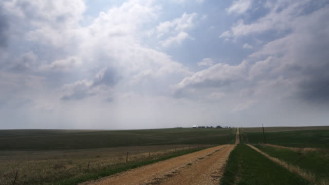 time-lapse clouds and their shadows race over the prairie toward farm buildings on the horizon - artbeats 個影片檔及 b 捲影像
