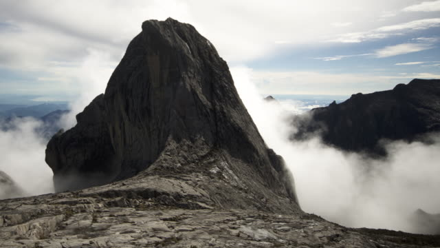 Timelapse clouds billow over rocky peak, Mount Kinabalu, Borneo