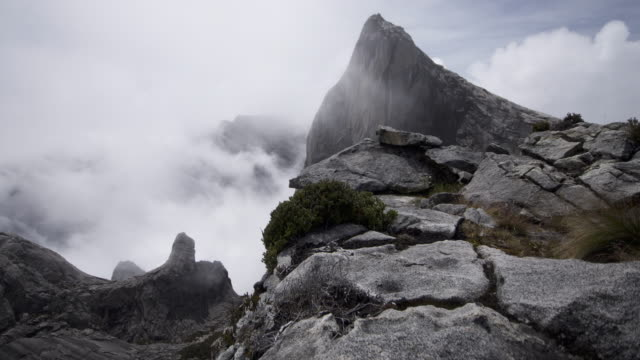 timelapse clouds billow over rocky peaks, mount kinabalu, borneo - borneo stock-videos und b-roll-filmmaterial