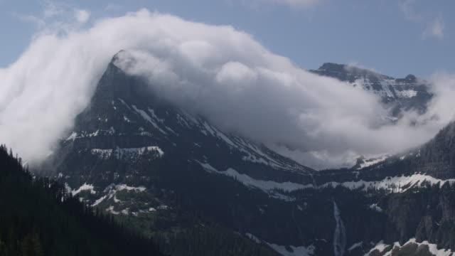 timelapse clouds billow over snowy rocky mountain peak, glacier national park, usa - モンタナ州点の映像素材/bロール