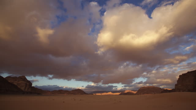 Timelapse clouds drift over desert valley at sunset, Wadi Rum, Jordan