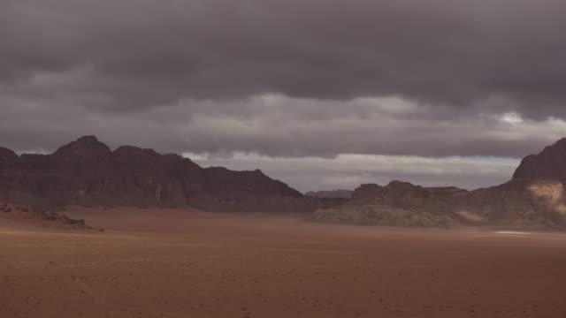 timelapse clouds drift over desert valley, wadi rum, jordan - arid stock videos and b-roll footage