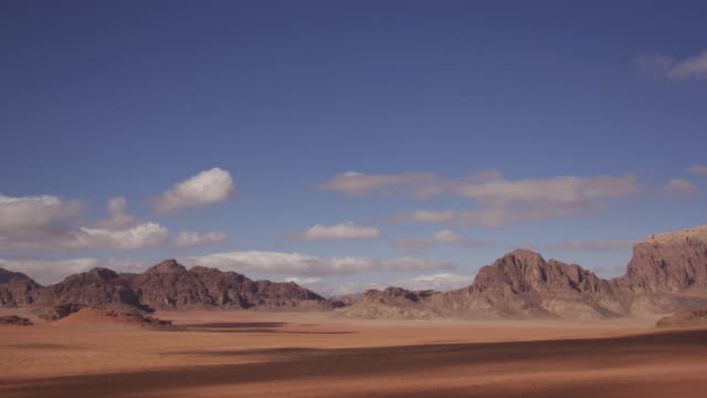 Timelapse clouds drift over desert valley, Wadi Rum, Jordan