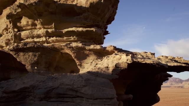 Timelapse clouds drift over eroded rock in desert valley, Wadi Rum, Jordan