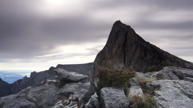 Timelapse clouds drift over rocky peak, Mount Kinabalu, Borneo