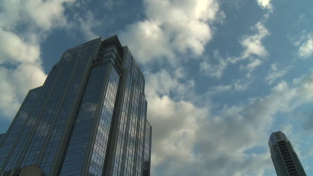 time-lapse: clouds float past buildings - austin texas stock videos & royalty-free footage