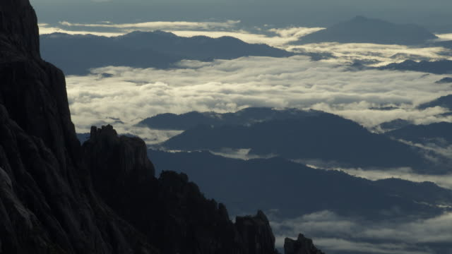 Timelapse clouds over forest below rocky peak, Mount Kinabalu, Borneo