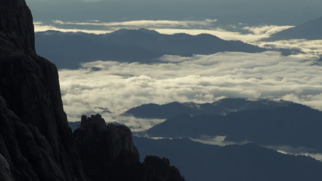 timelapse clouds over forest below rocky peak, mount kinabalu, borneo - sabah state stock videos and b-roll footage