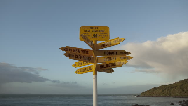 Time-lapse clouds pass behind a sign at the southernmost point of the South Island, New Zealand.