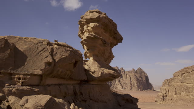 vidéos et rushes de timelapse clouds scud over eroded rock stack in desert, wadi rum, jordan - roche sédimentaire