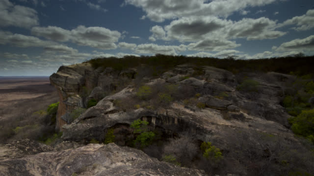 Timelapse clouds scud over rocky outcrop.
