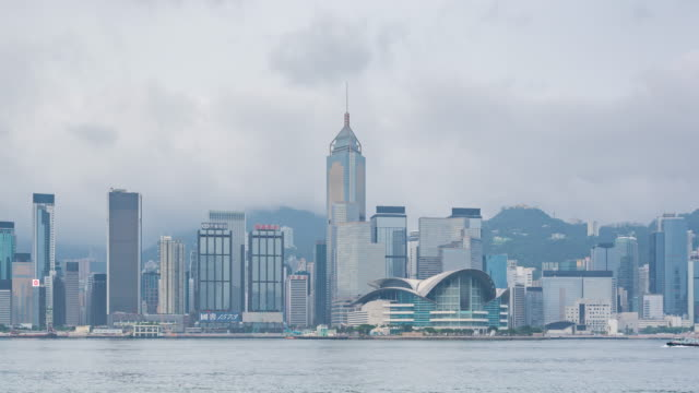 Timelapse cloudy Victoria bay and buildings infrastructure central in Hong Kong - Victoria harbor with modern business building exterior district city