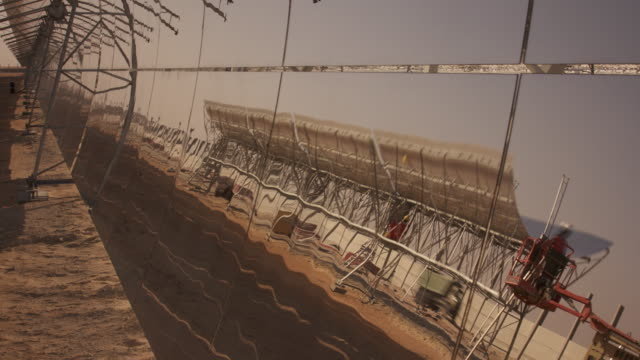 Timelapse construction reflected in solar panel at sunset, Masdar, Abu Dhabi