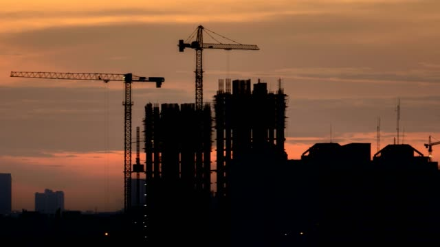 4k time-lapse: construction site at sunset, panning shot - crane stock videos & royalty-free footage