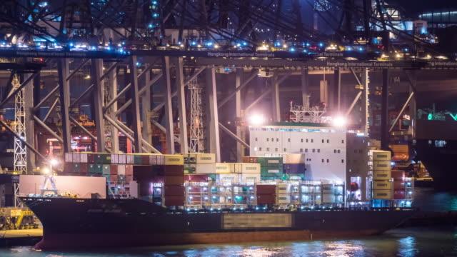 stockvideo's en b-roll-footage met time-lapse: container laden naar vrachtschip vracht bij maritieme containerport tsing yi haven van hong kong 's nachts - scheepvaart