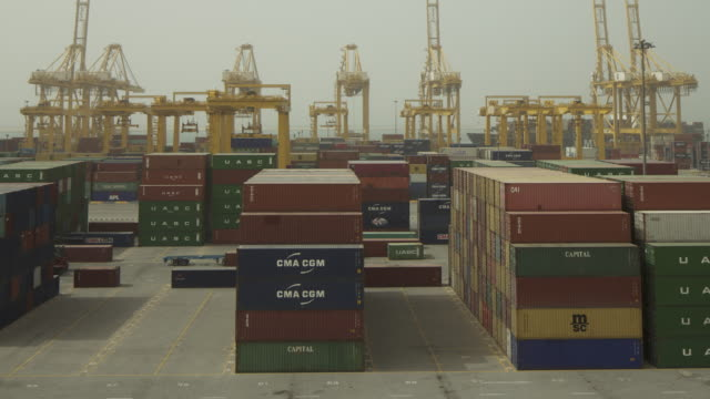 Timelapse cranes place containers onto lorries at port, Jebel Ali, Dubai