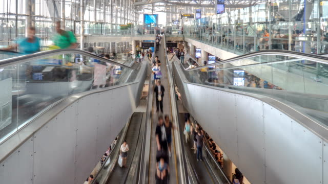 4k timelapse - crowds moving on escalators in the airport - airport terminal stock videos & royalty-free footage