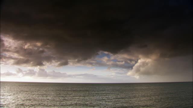 Timelapse dark clouds drift over calm Irish sea, UK