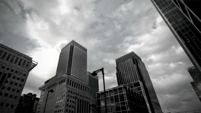 time-lapse. dark clouds over canary wharf - black and white stock videos & royalty-free footage