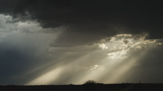 vídeos y material grabado en eventos de stock de time-lapse dark clouds pierced by sunbeams glide across the prairie at dusk - artbeats