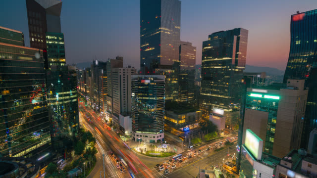 timelapse day to night at sunset of light trails traffic speeds through an intersection in gangnam center business district of seoul at seoul city, south korea. - zoom out stock videos & royalty-free footage
