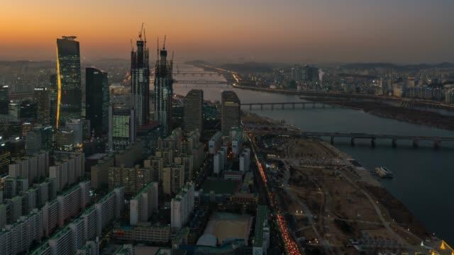 汝矣島の韓国ソウル市漢江を渡る橋の上車のトラフィックとビジネス地区の夜のタイムラプス日 - 昼から夜点の映像素材/bロール