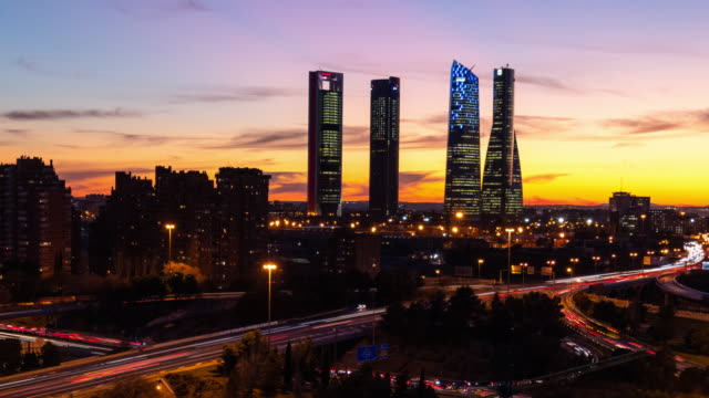 vídeos y material grabado en eventos de stock de time-lapse day to night sunset of the four tower business center in madrid - panorama urbano