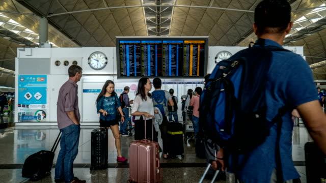 4k timelapse - departure board, hong kong international airport - hong kong international airport stock videos and b-roll footage