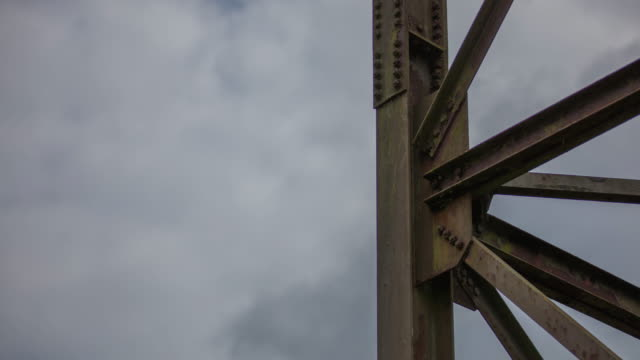 timelapse detail of weathered steel tower and moving clouds. - weathered stock videos and b-roll footage