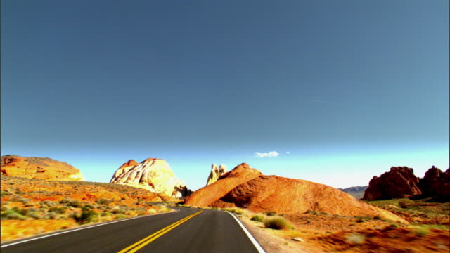 timelapse driving pov over two lane desert road through sandstone formations in valley of fire  / overton, nevada, usa - car point of view stock videos & royalty-free footage