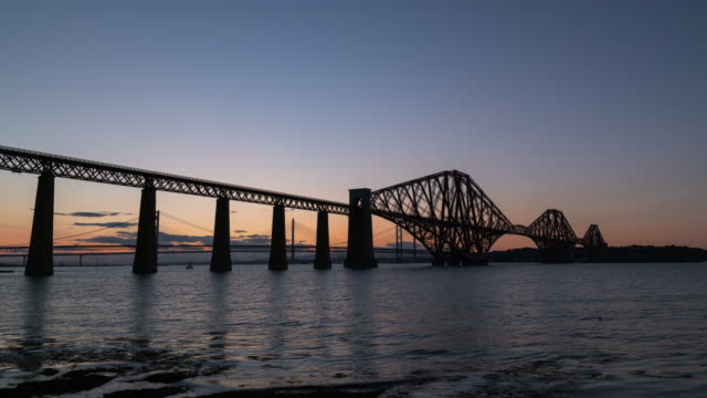 timelapse during sunset of the iconic forth bridge in edinburgh - fluss firth of forth stock-videos und b-roll-filmmaterial