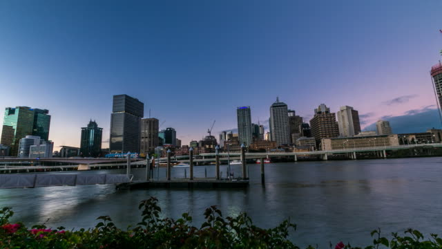 Timelapse Dusk to Night View over Brisbane River towards city Reflection of light on the Brisbane River as boats and ferries pass Brisbane city in...