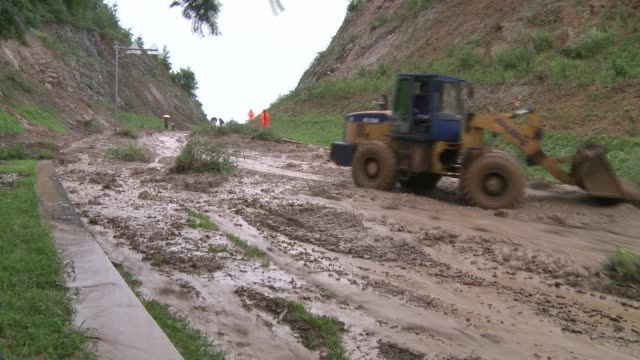 timelapse - earth mover clearing mudslide in road. - earth mover stock videos & royalty-free footage
