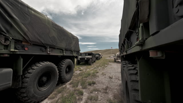 time-lapse filmed between covered convoy trucks at a military training. - convoy trucks stock videos and b-roll footage