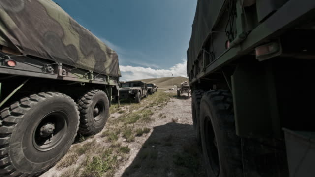 time-lapse filmed between military convoy trucks. - convoy trucks stock videos and b-roll footage