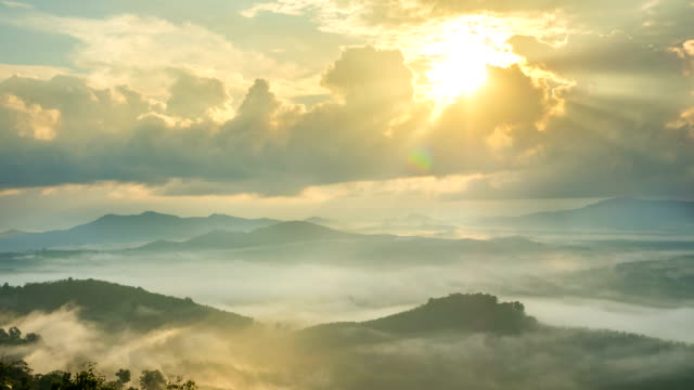 vídeos de stock e filmes b-roll de time-lapse fog above mountain and sunlight through clouds at sunrise in thailand - no alto