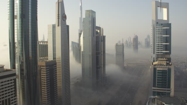 Timelapse fog drifts between buildings and over Sheikh Zayed road, Dubai